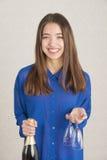 Mujer joven atractiva que sostiene la botella del champán y dos vidrios Fotos de archivo libres de regalías
