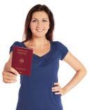 Mujer joven atractiva que sostiene un pasaporte alemán Imágenes de archivo libres de regalías