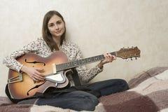 Mujer joven atractiva que toca la guitarra. Fotos de archivo libres de regalías