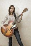 Mujer joven atractiva que toca la guitarra Imagenes de archivo
