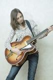 Mujer joven atractiva que toca la guitarra Fotos de archivo libres de regalías