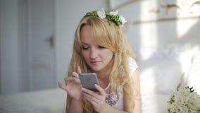 Mujer joven atractiva que usa el app en smartphone en el dormitorio tiro del steadicam almacen de video