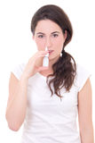 Mujer joven atractiva que usa el espray nasal aislado en blanco Imagenes de archivo