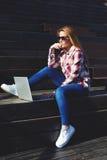 mujer joven atractiva que usa el ordenador portátil que se sienta en la escalera de madera que disfruta de día soleado al aire li Fotos de archivo