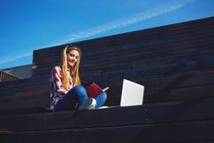 mujer joven atractiva que usa el ordenador portátil que se sienta en la escalera de madera que disfruta de día soleado al aire li Imagen de archivo