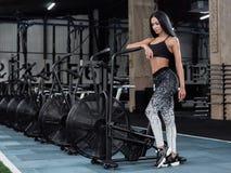 Mujer joven, atractiva que usa la bicicleta estática en el gimnasio Aptitud Foto de archivo