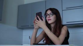 Mujer joven atractiva que usa su teléfono celular móvil que se sienta en la cocina almacen de metraje de vídeo