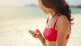 Mujer joven atractiva que usa su teléfono en la playa almacen de video