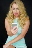 Mujer joven atractiva que usa un teléfono móvil foto de archivo