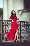 Mujer joven atractiva sensual elegante en el vestido rojo que presenta cerca de una barandilla Fotos de archivo libres de regalías