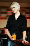Mujer joven atractiva sonriente que bebe el zumo de naranja Fotos de archivo