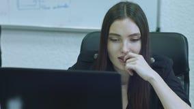 Mujer joven atractiva usando el ordenador en su lugar de trabajo Concentran al oficinista que hace su trabajo almacen de video