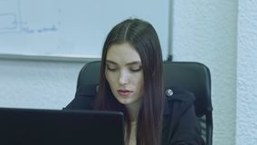 Mujer joven atractiva usando el ordenador en su lugar de trabajo Concentran al oficinista que hace su trabajo almacen de metraje de vídeo