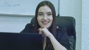Mujer joven atractiva usando el ordenador en su lugar de trabajo Oficinista que sonríe y que mira la cámara almacen de metraje de vídeo