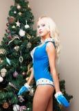 Mujer joven atractiva virginal de la nieve en un traje azul y guantes en el árbol de navidad Colocación en perfil Año Nuevo, la N Imagenes de archivo