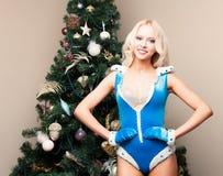 Mujer joven atractiva virginal de la nieve rubia hermosa en un traje azul y guantes en el árbol de navidad Año Nuevo, la Navidad, Fotografía de archivo libre de regalías