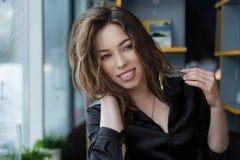 Mujer joven atractiva y alegre que sonr?e en caf? fotografía de archivo libre de regalías