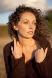 Mujer joven azotada por el viento en puesta del sol Fotos de archivo libres de regalías