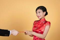 Mujer joven bastante china que recibe el bolsillo rojo por Año Nuevo chino feliz Imagenes de archivo