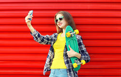 Mujer joven bastante fresca en gafas de sol con el monopatín Fotografía de archivo