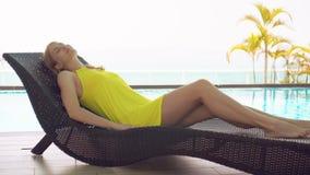 Mujer joven bastante soñadora en el vestido amarillo que miente en sunbed cerca de piscina del agua de la turquesa