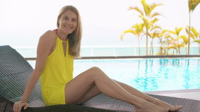 Mujer joven bastante soñadora en el vestido amarillo que se sienta en sunbed cerca de piscina del agua de la turquesa