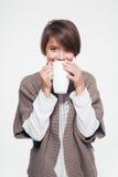 Mujer joven bastante sonriente en té de consumición hecho punto de la chaqueta Fotos de archivo