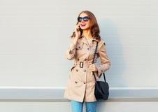 Mujer joven bastante sonriente que habla en el smartphone que lleva una capa y soportes negros del embrague del bolso sobre gris Fotografía de archivo