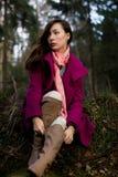 Mujer joven bien vestida en el abrigo rosado que se sienta en bosque Imagen de archivo libre de regalías