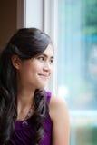 Mujer joven biracial hermosa que sonríe por la ventana Imagen de archivo