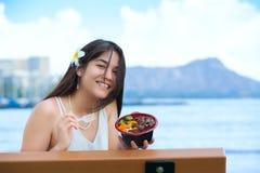 Mujer joven Biracial que come Bbq hawaiano, Diamond Head en backg Imagenes de archivo