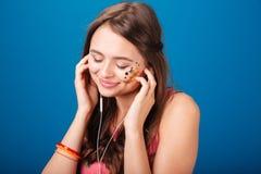 Mujer joven blanda hermosa que escucha la música usando los auriculares Imágenes de archivo libres de regalías
