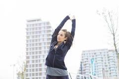 Mujer joven bonita con los auriculares que estiran durante traini del deporte foto de archivo libre de regalías