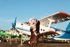 Mujer joven bonita de los businees en las faldas y los vidrios de cuero cerca del aeroplano antiguo Forma de vida, el viajar y te imagen de archivo