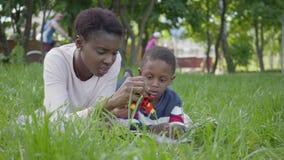 Mujer joven bonita del afroamericano lindo adorable del retrato que miente en la manta con su peque?o hijo que juega con un jugue almacen de video