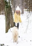 Mujer joven bonita en el invierno Forest Park Walking Playing Nevado con su samoyedo blanco del perro fotografía de archivo libre de regalías