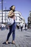 Mujer joven bonita que camina abajo de la calle imagen de archivo