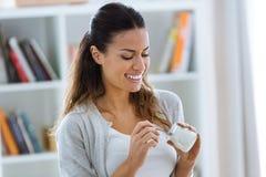 Mujer joven bonita que come el yogur en casa foto de archivo
