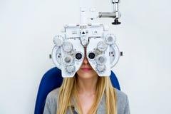 Mujer joven bonita que hace la medida de la vista con el phoropter óptico en clínica de la oftalmología foto de archivo