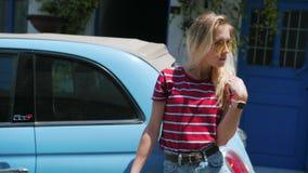 Mujer joven bonita que lleva la camisa roja en la pequeña calle europea delante del coche retro almacen de video