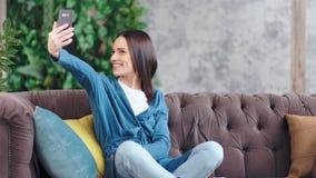 Mujer joven bonita que presenta y que goza haciendo el selfie usando smartphone en la sala de estar de lujo almacen de metraje de vídeo