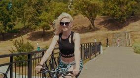 Mujer joven bonita que sonríe mientras que monta su bicicleta en día de verano soleado en slomo metrajes