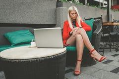 Mujer joven bonita que trabaja en el ordenador portátil y que comprueba tiempo en su reloj foto de archivo libre de regalías