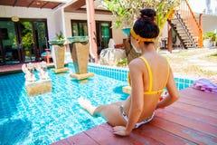 Mujer joven bonita sonriente que se sienta cerca de la piscina que bebe un cóctel imagenes de archivo