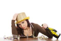 Mujer joven borracha que se sienta con la botella vacía del champán. Imágenes de archivo libres de regalías