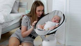 Mujer joven borrosa que mira un pequeño sueño lindo del bebé en cama en casa metrajes