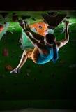Mujer joven bouldering en techo del gimnasio que sube Imagen de archivo libre de regalías