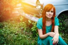 Mujer joven brillante que presenta cerca del coche viejo Fotografía de archivo libre de regalías