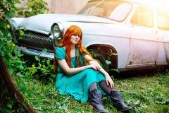 Mujer joven brillante que presenta cerca del coche viejo Fotografía de archivo