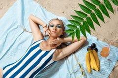 Mujer joven bronceada que toma el sunbath malsano en un día de verano en una playa que oculta del sol con el sombrero y los vidri Fotografía de archivo libre de regalías